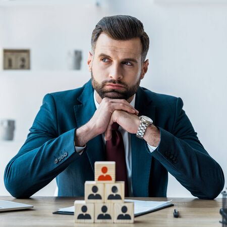 selective focus of pensive and bearded man with clenched hands near wooden cubes Banque d'images