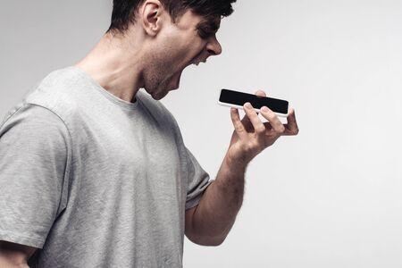 aggressive man screaming on smartphone isolated on grey 版權商用圖片