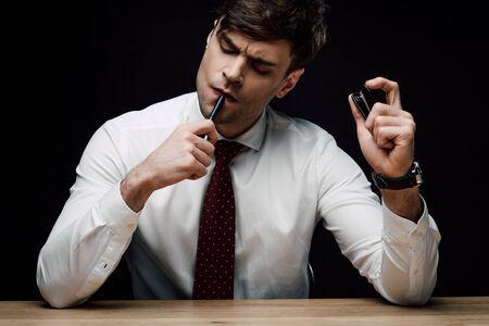 Empresario pensativo sosteniendo grapadora y bolígrafo aislado en negro Foto de archivo