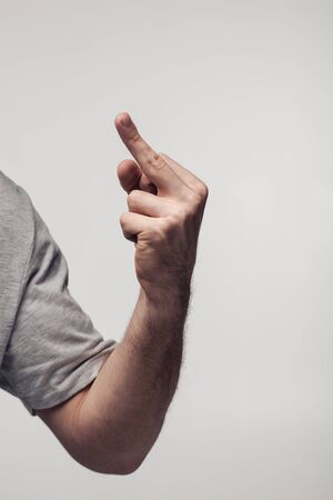 partial view of man showing middle finger isolated on grey, human emotion and expression concept