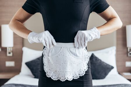 partial view of maid in white gloves and apron in hotel room