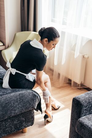 Criada cansada en guantes blancos tocando las piernas mientras está sentado en la cama