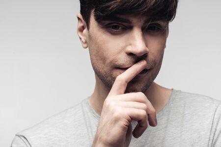 nachdenklicher stummer Mann, der Stillegeste einzeln auf grauem, menschlichem Emotions- und Ausdruckskonzept zeigt