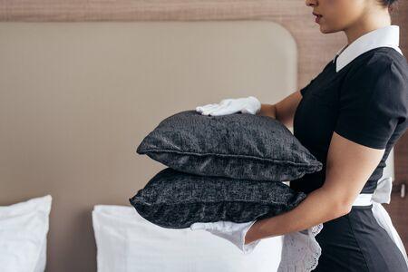 Ausgeschnittene Ansicht der Magd in weißen Handschuhen, die Kissen im Hotelzimmer hält?