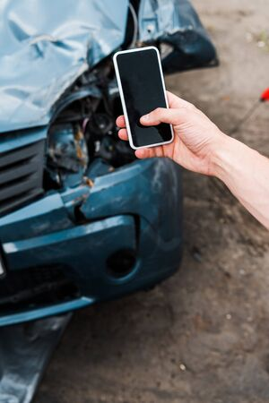 selective focus of man holding smartphone with blank screen near damaged car