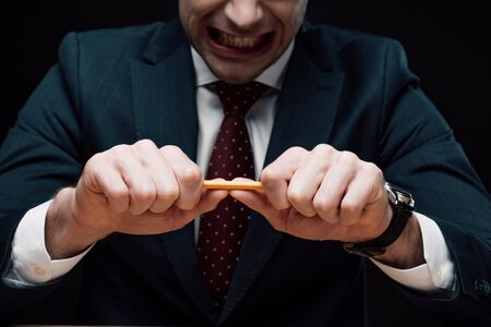 partial view of irritated businessman braking pencil isolated on black