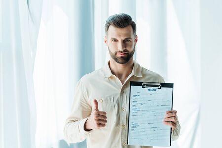Gut aussehender bärtiger Mann, der Daumen nach oben zeigt und die Zwischenablage mit Lebenslaufbuchstaben hält holding