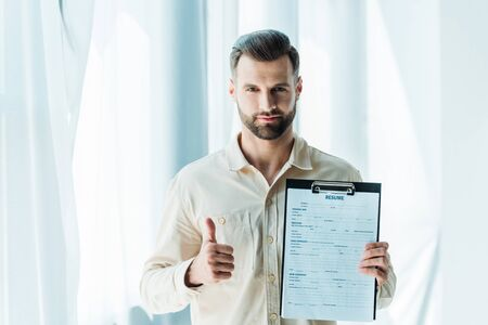 handsome bearded man showing thumb up and holding clipboard with resume letters Фото со стока