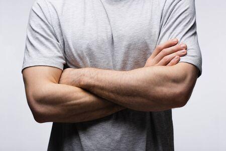 Vista recortada del hombre de pie con los brazos cruzados aislado en gris, la emoción humana y el concepto de expresión