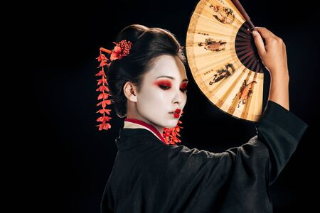 side view of geisha in black kimono with red flowers in hair holding traditional asian hand fan isolated on black