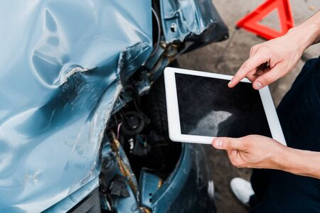 cropped view of man pointing with finger at digital tablet with blank screen near crashed car