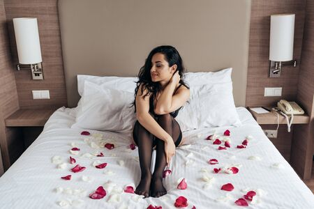 sexy brunette girl in black stockings sitting on bed with rose petals in bedroom 写真素材 - 128157757