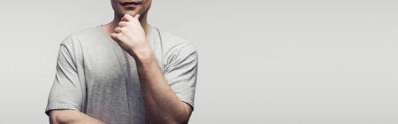 cropped view of man holding hand near face isolated on grey, panoramic shot, human emotion and expression concept Banco de Imagens