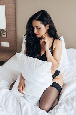 mujer joven, en, lenceria, tenencia, almohada blanca, en, dormitorio Foto de archivo
