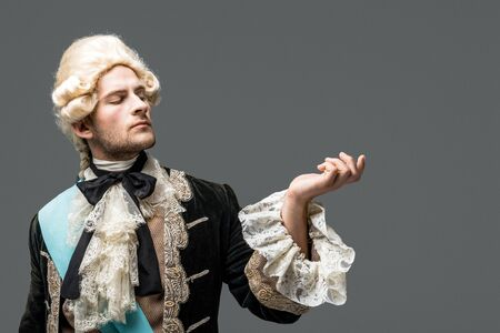 pompous victorian gentleman in wig standing and gesturing isolated on white 스톡 콘텐츠