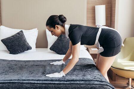 Pretty maid en guantes blancos limpiando la cama en la habitación del hotel