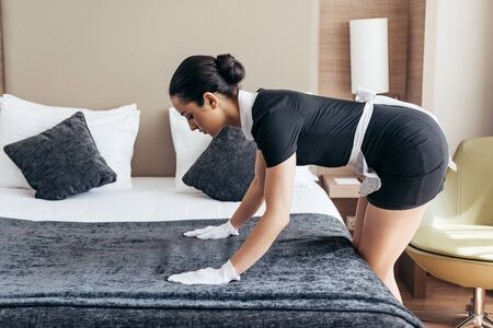 pretty maid in white gloves cleaning bed in hotel room