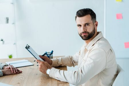 cropped view of recruiter near handsome bearded man looking at camera while holding clipboard Stock Photo