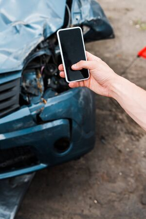 selective focus of man holding smartphone with blank screen near crashed car