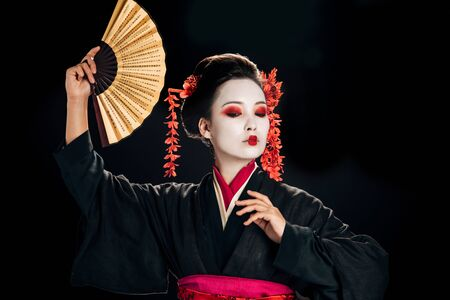 geisha in black kimono with red flowers in hair dancing with traditional asian hand fan isolated on black Stock Photo