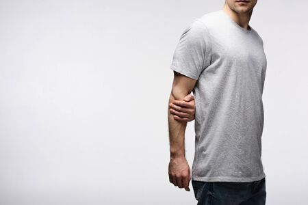 cropped view of man holding hand behind back isolated on grey, human emotion and expression concept