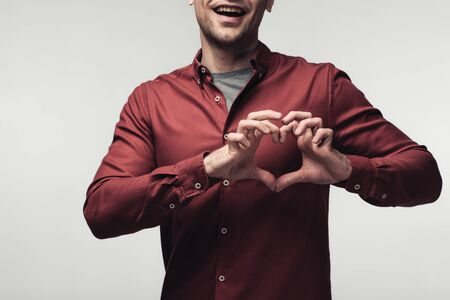 partial view of cheerful man showing heart sign with hands isolated on grey, human emotion and expression concept