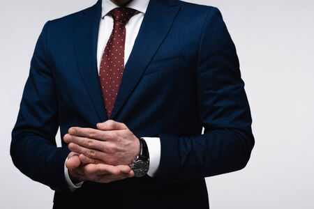 partial view of confident businessman gesturing with hands isolated on grey, human emotion and expression concept