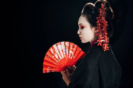 side view of beautiful geisha in black kimono with red flowers in hair holding traditional hand fan isolated on black Stock Photo