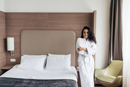 Atractiva mujer joven morena en bata de baño blanca de pie cerca de la cama en el acogedor dormitorio