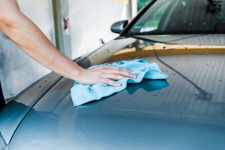 cropped view of man cleaning wet car with blue rag Foto de archivo - 128158000