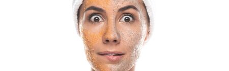 panoramic shot of shocked woman in cosmetic hair band with scrub on face isolated on white Stockfoto