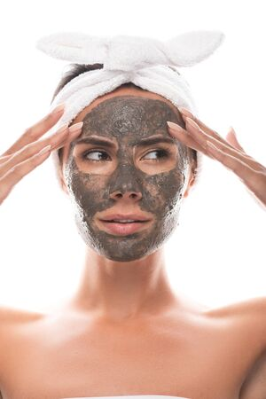front view of pensive nude young woman in cosmetic hair band with clay mask on face isolated on white