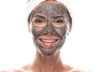 front view of smiling nude young woman in cosmetic hair band with clay mask on face isolated on white