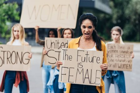front view of screaming african american feminist holding placard with inscription the future is female on street