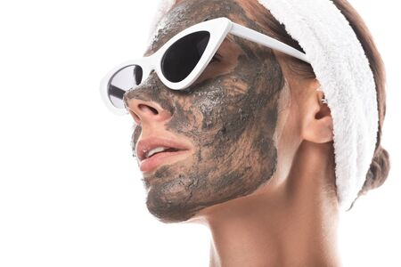 young woman in cosmetic hair band and sunglasses with clay mask on face isolated on white