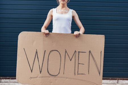 cropped view of feminist with word brave on body holding placard with inscription women on street Фото со стока
