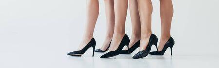 panoramic shot of three women wearing black high-heeled shoes on grey