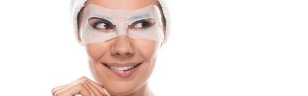 panoramic shot of smiling woman in cosmetic hair band with facial mask isolated on white