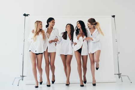 full length view of five sexy multiethnic girls wearing white shirts and heels smiling on grey