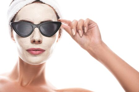 front view of woman in sunglasses and cosmetic hair band with facial mask isolated on white