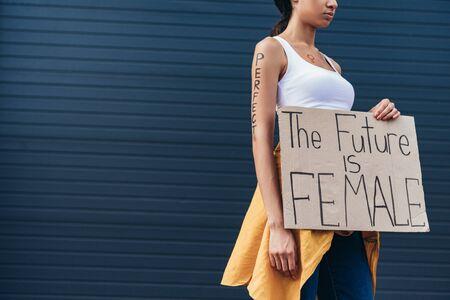 vue recadrée de féministe avec mot parfait sur le bras tenant une pancarte avec inscription l'avenir est une femme