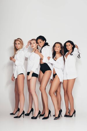 full length view of sexy feminists wearing heels and white shirts on grey Stock Photo