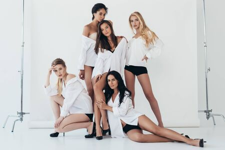 full length view of sexy multiethnic feminists wearing heels and white shirts on grey