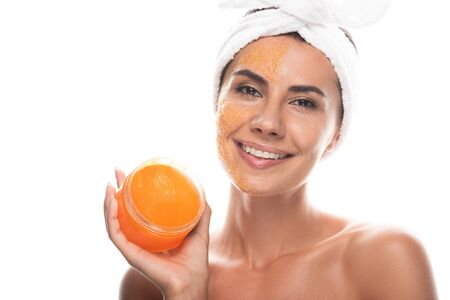 front view of smiling young woman in cosmetic hair band with scrub on face holding container isolated on white