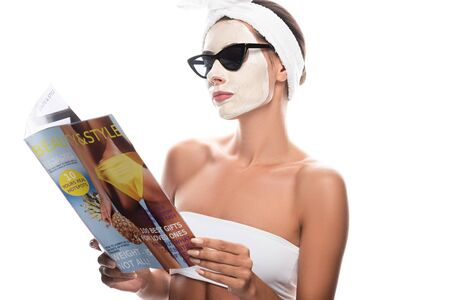 woman in cosmetic hair band and sunglasses with facial mask reading magazine isolated on white