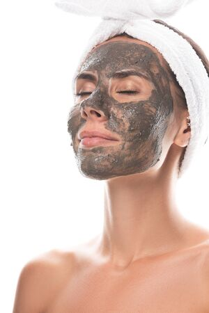 nude young woman in cosmetic hair band with clay mask on face with closed eyes isolated on white