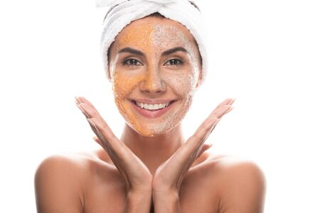 front view of excited young woman in cosmetic hair band with scrub on face isolated on white Stockfoto