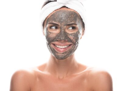 front view of nude young woman in cosmetic hair band with clay mask on face isolated on white