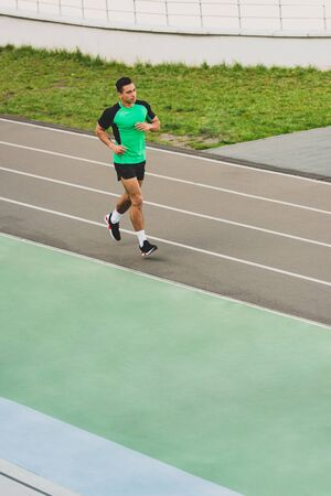 full length view of mixed race sportsman running at stadium