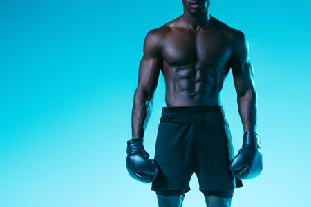 cropped view of african american sportsman in boxing gloves on blue background Archivio Fotografico - 129539536